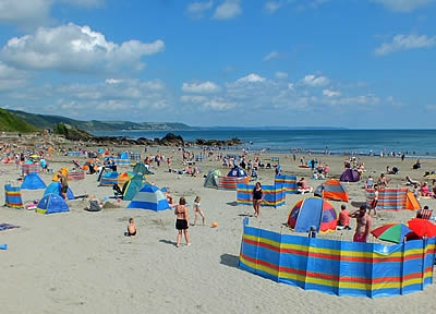 Holiday makers enjoying the summer sunshine on East Looe beach